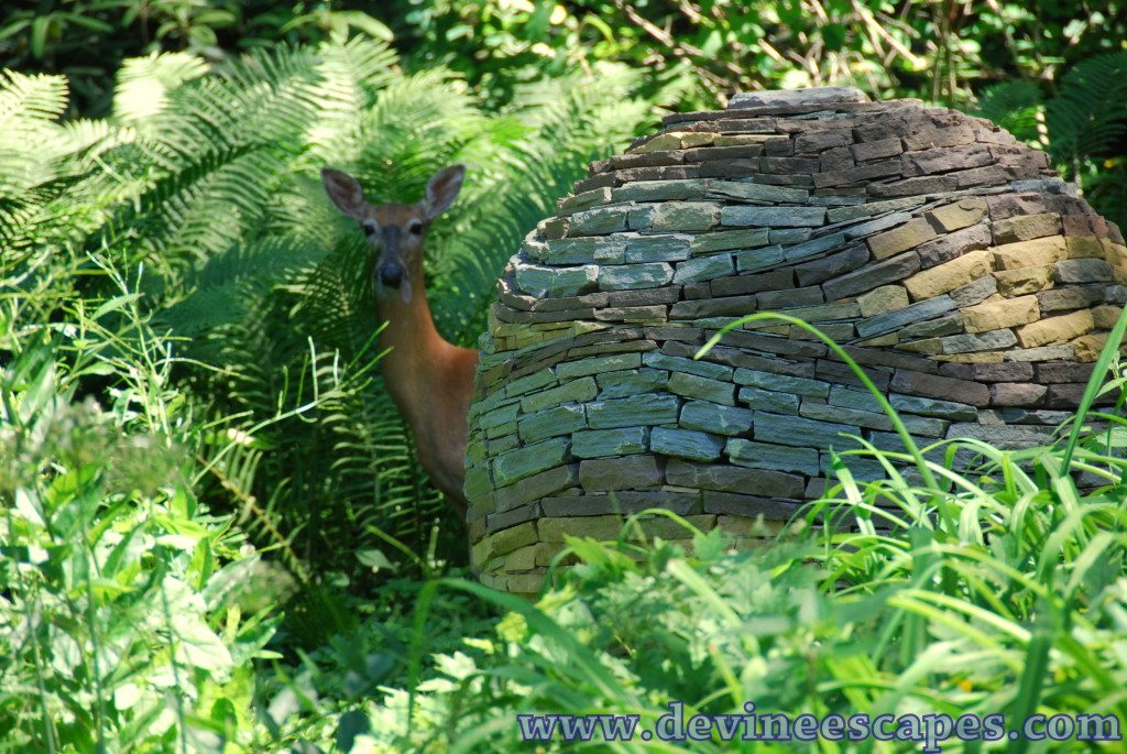 colorful dry stone sculpture with deer standing next to it